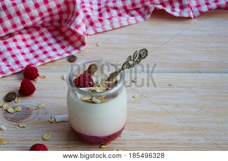 Close up of fruit on the bottom yogurt jar with raspberry and coconut on wooden background. Heathy eating cocnept.
