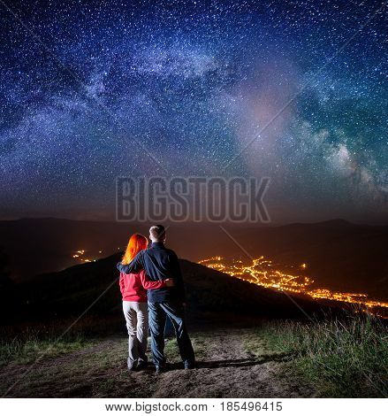 Rear View Romantic Couple Hugging Each Other, Standing On A Hill Under The Bright Stars, Looking On