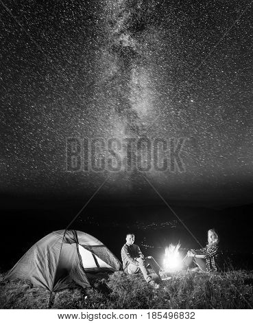Tourist Couple - Girl And Guy Sitting Near Campfire And Glowing Tent Under Incredibly Beautiful Star