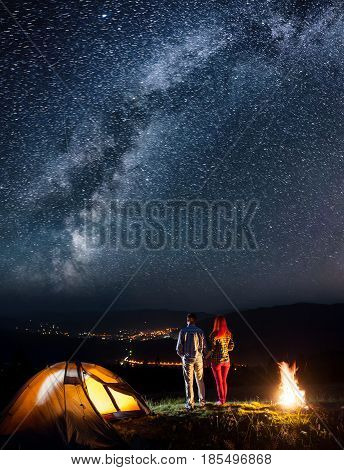 Happy Tourist Couple - Girl And Guy Holding Hands, Standing Near Tent And Enjoying Incredibly Beauti