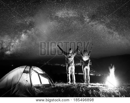 Romantic Pair Hikers Raised Their Hands Up Under The Stars Near Campfire And Tent, Looking On The St