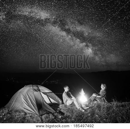 Night Tent Camping. Young Couple Hikers Sitting Near Fire Under Incredibly Beautiful Starry Sky And