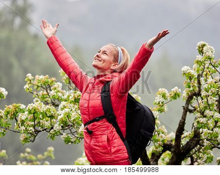 young woman walking through blooming orchard on foggy morning