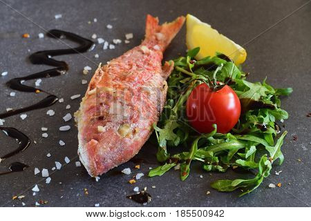 Grilled red mullet on a greay abstract background with rokka salad, balsamic glaze, lemon and cherry tomato. Healthy eating concept.