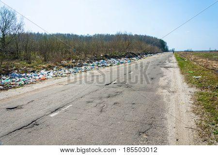 The piles of debris along the bad asphalt road Shuyskiy rayon Ivanovskaya oblast Russia.