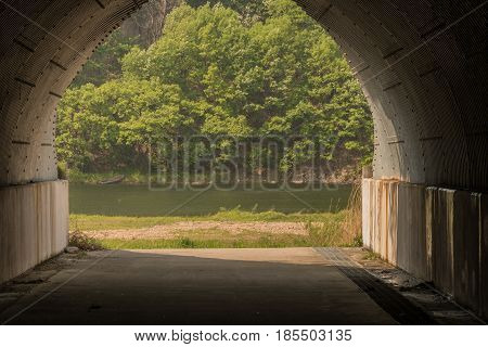 View of small boat on far tree lined river bank seen through a concrete underpass