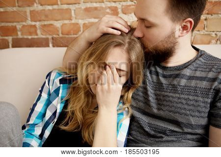 Young woman sitting on sofa with sinus pain, her partner is carring on her.