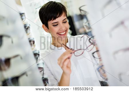health care eyesight and vision concept - happy beautiful woman choosing glasses at optics store