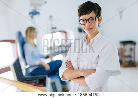 Beautiful young ophthalmologist doctor in eyesight clinic