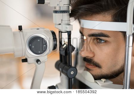 Patient or customer at slit lamp at optometrist or optician examining eyesight