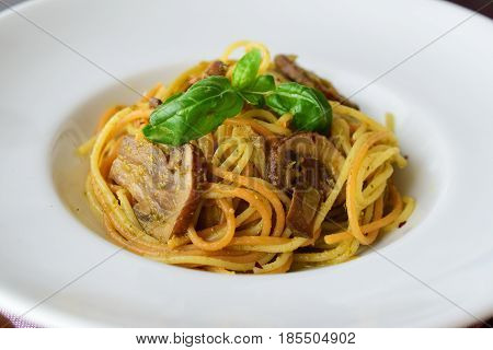 Pasta with mushroom.s and pesto sauce in a white plate on abstract bckground. Italian lifestyle. Healthy eating concept