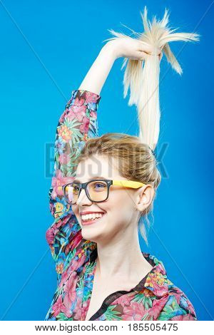 Joyful Girl in Fashionable Eyeglasses is Posing in Studio. Portrait of Funny Blonde Woman with Ponytail Wearing Colorful Shirt on Blue Background.