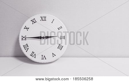 Closeup white clock for decorate show a quarter to three o'clock or 2:45 p.m. on white wood desk and wallpaper textured background in black and white tone with copy space