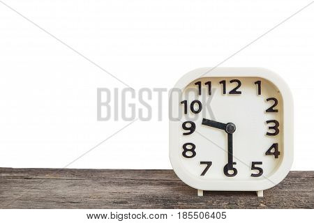 Closeup white clock for decorate show half past nine o'clock or 9:30 a.m. on old brown wood desk isolated on white background with copy space