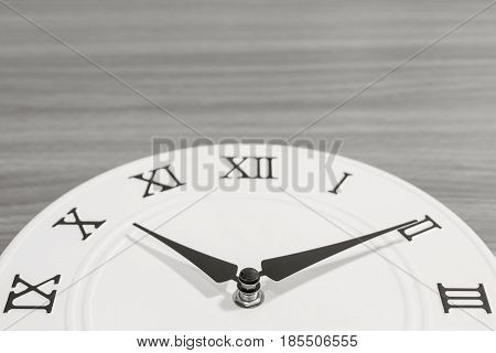 Closeup part of white clock for decorate in ten past ten o'clock on wood desk textured background in black and white tone with copy space
