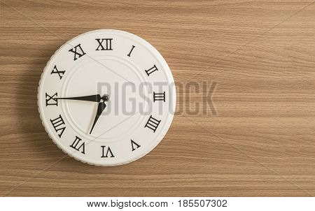 Closeup white clock for decorate show a quarter to seven or 6:45 a.m. on wood desk textured background with copy space