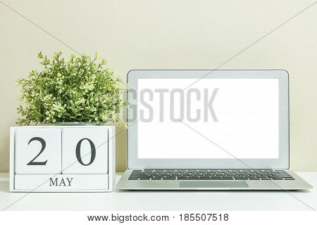 White wooden calendar with black 20 may word with white blank space at center of computer notebook on white wood desk and cream wallpaper textured background selective focus at the calendar