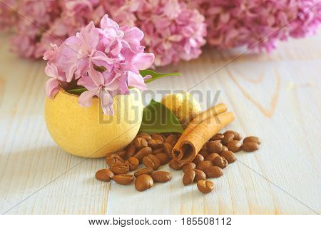 Coffee grains lilac purple flower still life background template. Vintage wooden table coffee beans cinnamon flavor decoration.