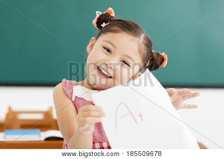 happy little girl showing exam paper with a plus in classroom