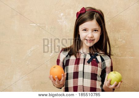 Happy Girl Smiling With Orange And Apple In Hands