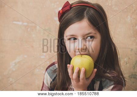 Adorable Girl Eating Vitamin Yellow Apple
