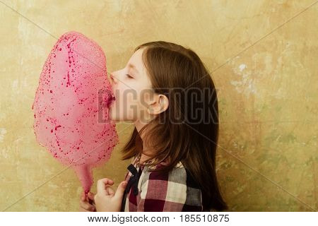 child or small little girl with long hair in plaid dress eating yummy pink cotton candy sweet sugar spun candyfloss on stick on beige background. Unhealthy food or snack