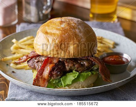 thick tasty bacon cheese burger on brioche bun served with fries on plate