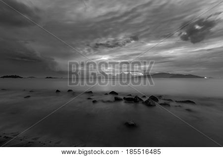 A moody black and white morning sky over Nha Trang bay Vietnam just before sunrise.