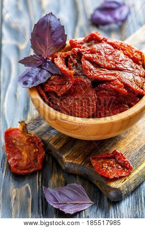 Sun-dried Tomatoes And Red Basil In A Wooden Bowl.