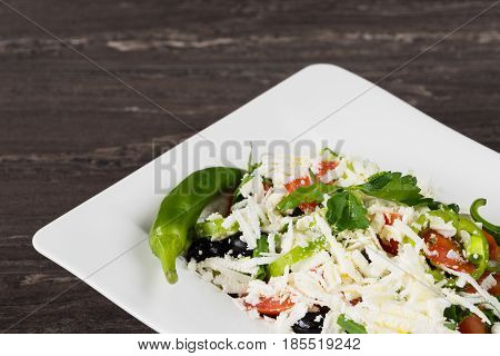 Traditional classic Shopska salad with tomatoes, peppers, cucumbers and cheese in white dish on grey wooden table. Bulgarian cuisine, Balkan culture