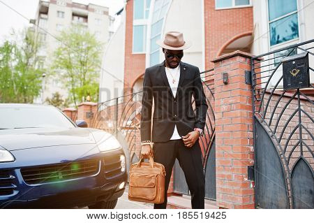 Stylish Black Man At Glasses With Hat, Wear On Suit With Handbag Against Luxury Car. Rich African Am