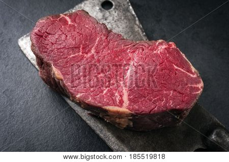 Dry aged raw Kobe Point Steak as close-up on a kitchen cleaver