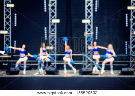 Blurred cheerleaders entertaining audience during sports competition