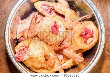 Several carcases of raw chicken in saucepan