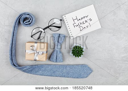 Happy Fathers Day background with notebook gift glasses necktie and bowtie on stone table top view in flat lay style.