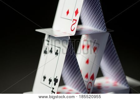 casino, gambling, games of chance, hazard and insecurity concept - close up of house of playing cards over black background