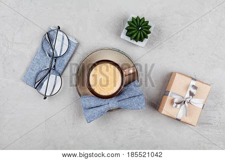Morning coffee mug gift glasses and bowtie on stone table top view in flat lay style for breakfast on Happy Fathers Day.