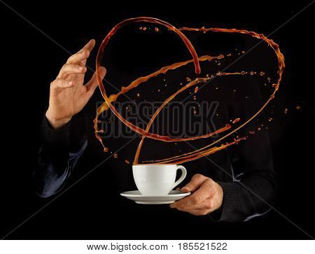 Man hands holding porcelain cup with splashing liquid of coffee or tea, isolated on black background. Hot drink with splashes, beverages and refreshment.
