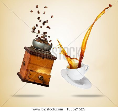 Porcelain white cup with splashing coffee and wooden grinder, separated on brown background. Hot drink with splash, beverages and refreshment.
