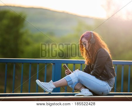 Red-haired girl with listening to music on a bridge at sunset