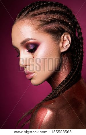 Portrait of beautiful woman with sparkles on her face. Girl with art make up in color light. Fashion model with colorful make-up