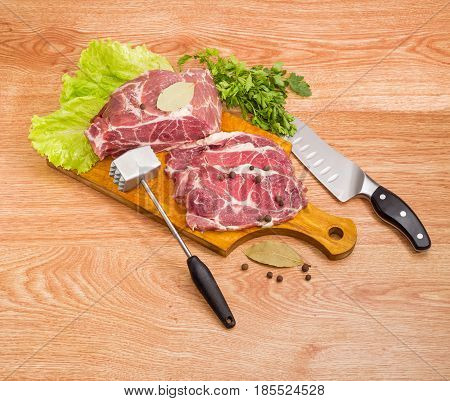 Partly sliced uncooked pork neck lettuce leaves and spices on wooden cutting board bunch of the parsley meat tenderizer and kitchen knife on a wooden surface