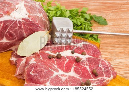 Partly sliced uncooked pork neck spices and parsley on wooden cutting board and meat tenderizer closeup on a wooden surface