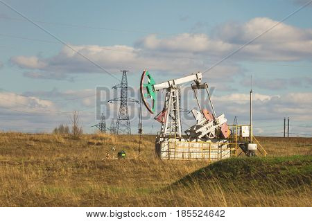 Oil pumpjack among grassy field at sunny day, telephoto