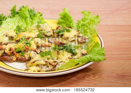 Fragment of the yellow and white dish with several pork chops baked with onion mushrooms and cheese and decorated with parsley and lettuce leaves on a wooden surface