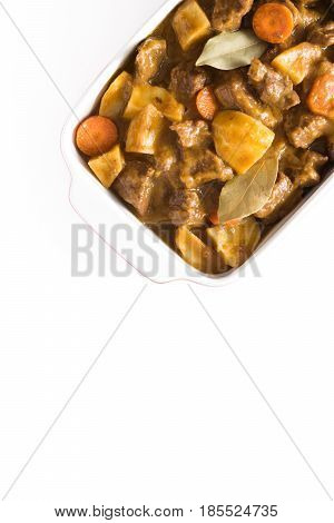 Beef meat stewed with potatoes, carrots and spices in ceramic pot isolated on white background.Top view