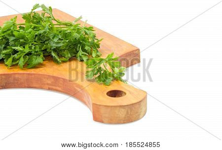 Fragment of the old wooden cutting board closeup and bunch of the fresh parsley on it on a light background