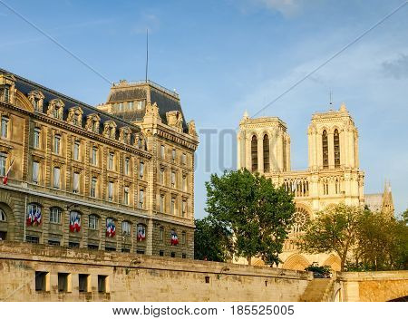 View of the west facade of the Cathedrale Notre-Dame de Paris and part of the building of Police prefecture from the Seine in the spring evening