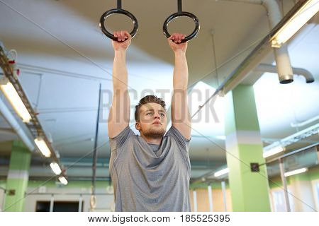 sport, fitness, training and people concept - man exercising and doing ring pull-ups in gym
