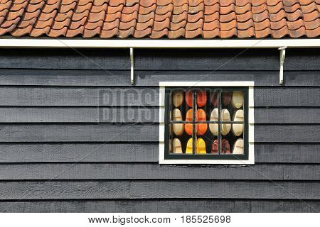 The wooden house of Netherlands and a window full of clogs inside.